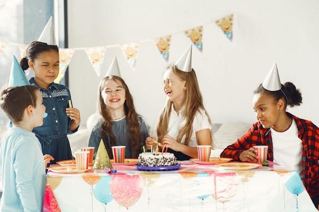 Lustige kindergeburtstagsfeier im dekorierten raum. glückliche kinder mit kuchen und luftballons.