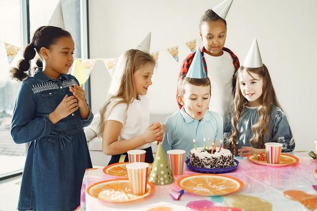 Lustige kindergeburtstagsfeier im dekorierten raum. glückliche kinder mit kuchen und luftballons. Kostenlose Fotos