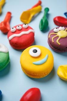 Lustige kinderleckerbissen für halloween: variationen von makronen, dekoriert in form verschiedener monster, geister.