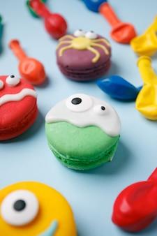 Lustige kinderleckerbissen für halloween: variationen von makronen, dekoriert in form von verschiedenen monstern