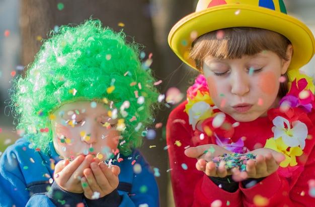 Lustige kindermädchen feiern karneval lächelnd und haben spaß mit bunten konfetti