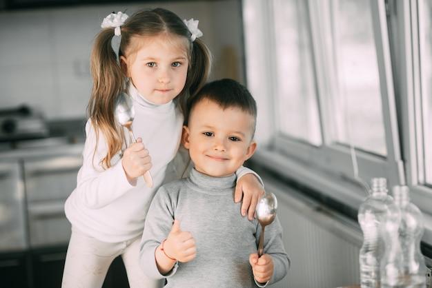 Lustige kindermädchen und -junge in der küche mit löffeln, spielen, niedlich essen