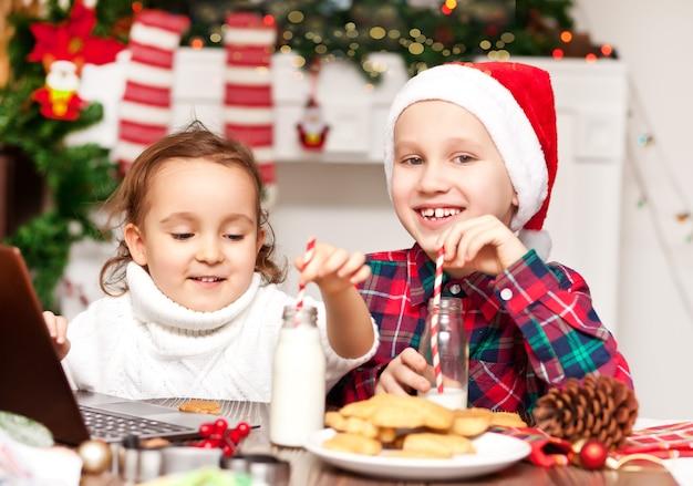 Lustige kindermädchen und -jungen in den weihnachtsmannmützen, die einen kakao mit marshmallows trinken.