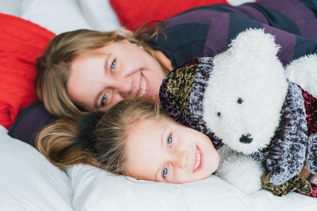 Lustige kindheit. liebevolle mutter machte ihre süße kleine tochter mit teddybär geschenk glücklich.