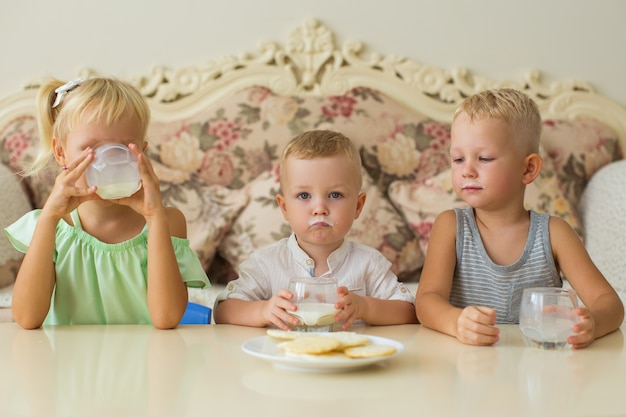 Lustige kleine jungen und mädchen, die milch zu hause trinken