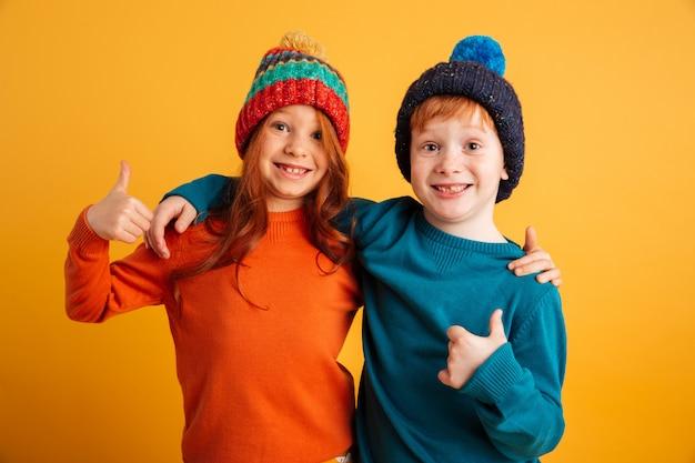 Lustige kleine kinder, welche die warmen hüte sich zeigen daumen tragen.