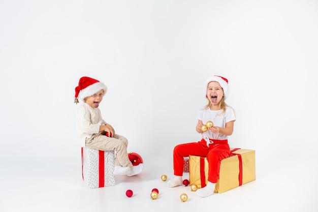 Lustige kleinkinder in der weihnachtsmannmütze, die auf geschenkboxen sitzt und zeigen ihre zungen. isoliert auf weißem hintergrund