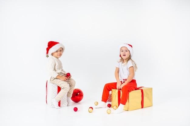 Lustige kleinkinder in sankt-hut, der auf geschenkboxen sitzt. isoliert auf weißem hintergrund