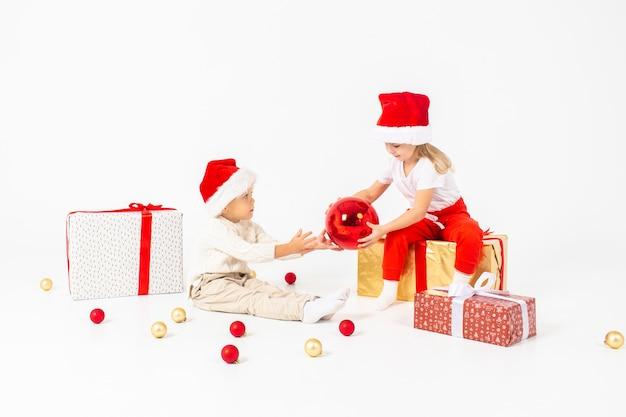 Lustige kleinkinder in sankt-hut, der auf geschenkboxen sitzt.