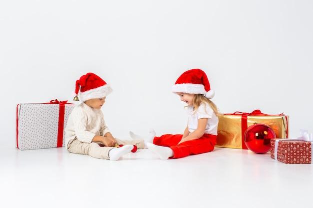 Lustige kleinkinder in sankt-hut, der zwischen geschenkboxen sitzt und mit weihnachtsbällen spielt