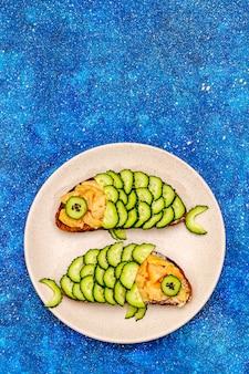 Lustige lachssandwiches mit gurke in fischform