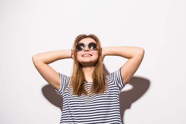 Lustige lässige teenagerfrau, die mode-sonnenbrille trägt, gestikuliert auf einer weißen wand