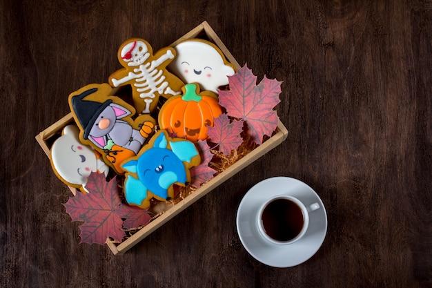 Lustige lebkuchenplätzchen für halloween. weihnachtskuchen liegen in einer schachtel neben einer tasse tee.