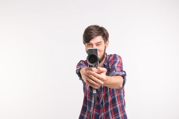 Lustige leute, foto- und vintage-konzept - junger mann mit vintage-kamera auf weißem hintergrund
