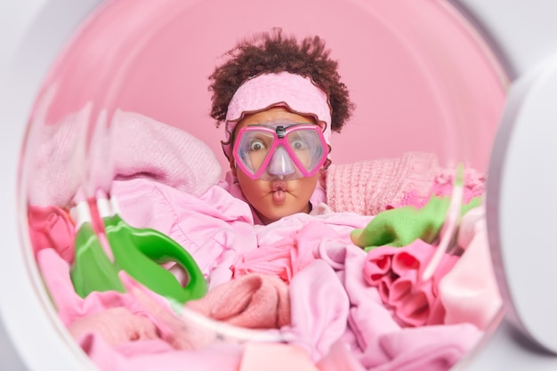 Lustige lockige junge frau macht grimasse fischlippen trägt schnorchelmaske posen aus der waschmaschine bereitet sich auf den waschprozess vor, umgeben von einem haufen schmutziger kleidung zum waschen