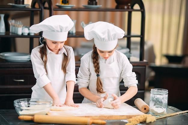 Lustige mädchen bereiten den teig in der küche zu.