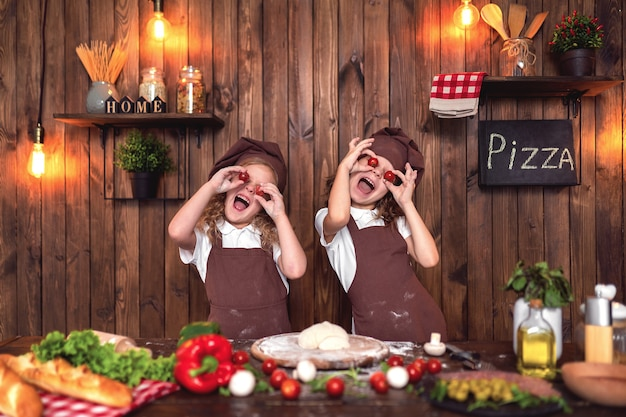 Lustige mädchen, die pizza kochen und mit tomaten täuschen