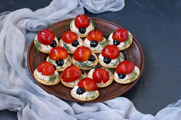 Lustige marienkäfer-snack-vorspeise mit tomate auf crackern mit käse auf dunklem hintergrund