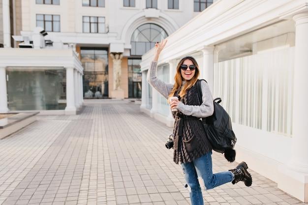 Lustige modische frau, die wahre positive emotionen im stadtzentrum zeigt. junge frau mit kaffee zum mitnehmen, reisen mit tasche und kamera, wollpullover, sonnenbrille, spaß haben. platz für text.