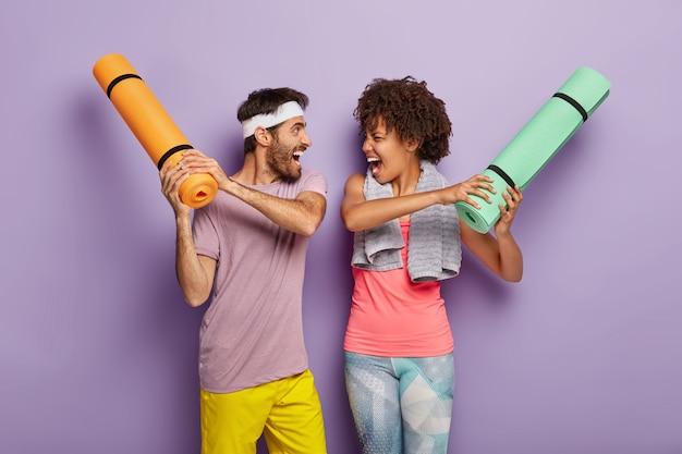 Lustige multiethnische frau und mann haben spaß im fitnessstudio, kämpfen mit aufgerollten karematen