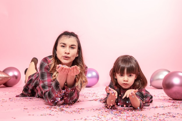 Lustige mutter und kind liegen auf einem rosa raum. kleines mädchen und mutter, die spaß mit konfetti haben