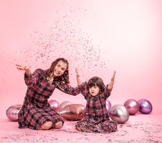 Lustige mutter und kind sitzen auf einem rosa hintergrund. kleines mädchen und mutter, die spaß mit luftballons und konfetti haben