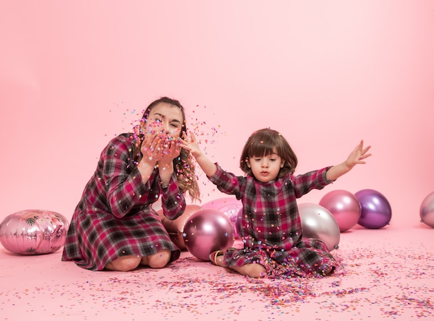 Lustige mutter und kind sitzen auf einer rosa wand. kleines mädchen und mutter haben spaß mit luftballons und konfetti