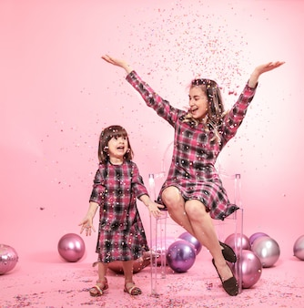 Lustige mutter und kind sitzen auf einer transparenten rosa wand der stilvollen stühle. kleines mädchen und mutter haben spaß mit luftballons und konfetti