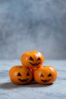 Lustige orange mandarinen oder mandarinen sehen aus wie kürbis jack o laterne