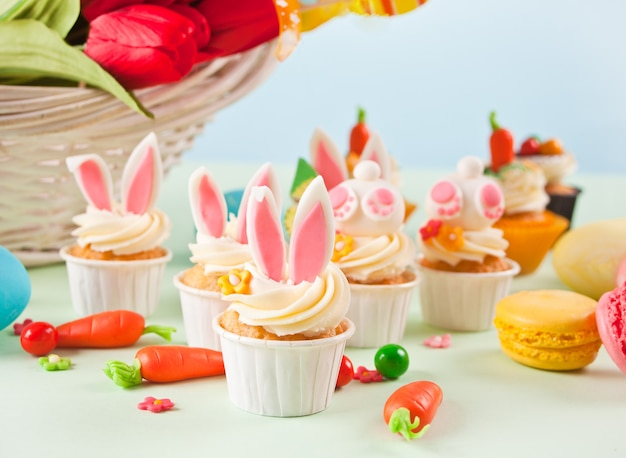 Lustige osterhasen-cupcakes. osterfeier festlicher tisch. blumenkorb tulpen auf dem hintergrund.