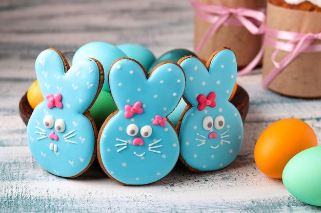 Lustige osterhasen, hausgemachte gemalte lebkuchenplätzchen in glasur und gemalte eier