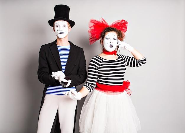 Lustige paar pantomimen, die durch die telefone sprechen. konzept des aprilscherzes