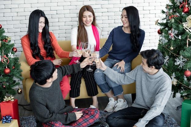 Lustige party des jungen asiaten mit klirrgläsern und trank wein zu hause, um weihnachtsfest zu feiern