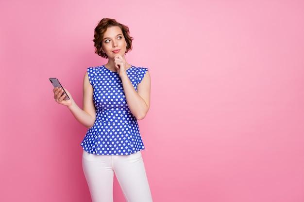 Lustige pin-up-stil junge dame hält telefon finger kinn blick leeren raum