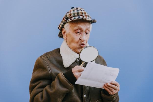 Lustige porträts mit alter großmutter. ältere frau als ermittlerin mit der vergrößerungslinse