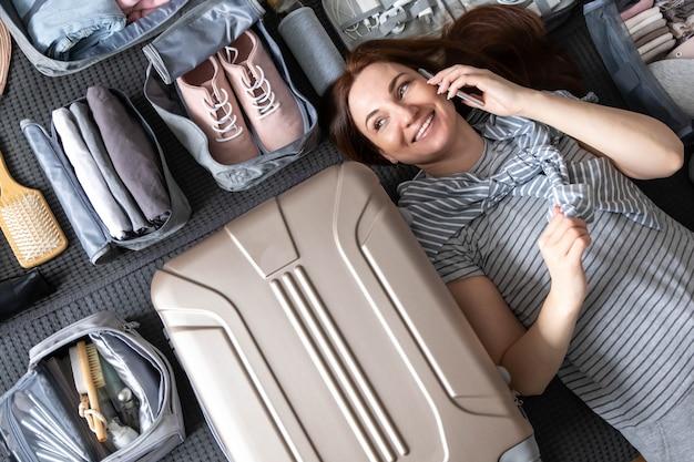 Lustige reisefrau, die auf dem bett liegt und müde müdes packen des smartphones spricht, um reiseurlaub zu reisen