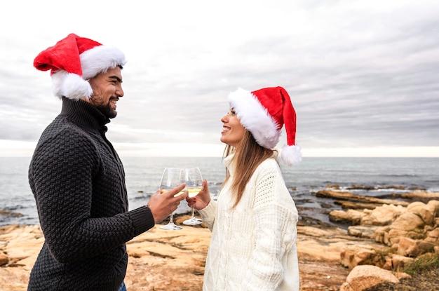 Lustige romantikszene eines schönen glücklichen jungen paares, das weihnachten im freien stehend feiert
