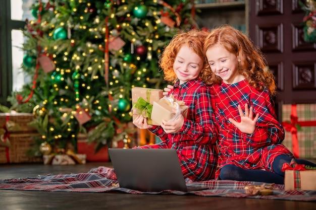 Lustige rothaarige kinder neben dem weihnachtsbaum und geschenke kommunizieren online über einen laptop.