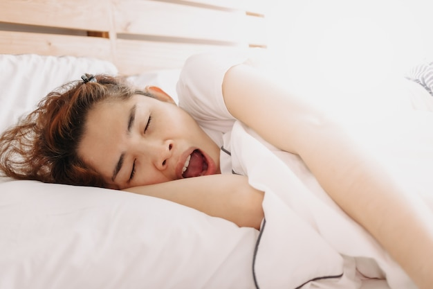 Lustige schläfrige gähnende frau wacht gerade auf ihrem bett auf