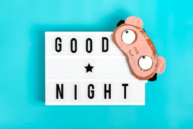 Lustige schlafmaske und leuchtkasten mit zitat gute nacht auf blauem hintergrund