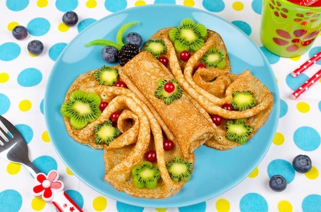 Lustige schmetterlingsgesichtspfannkuchen mit beeren und früchten für kinder snacks