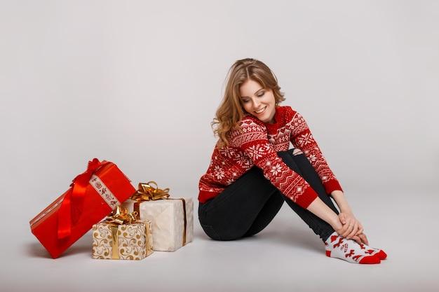 Lustige schöne frau im vintage roten pullover sitzt in der nähe von geschenken auf einem grauen hintergrund