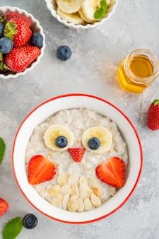 Lustige schüssel mit haferbrei mit eulengesichtern aus früchten und beeren auf grauem betonhintergrund. essen für kinderidee, draufsicht, kopienraum.
