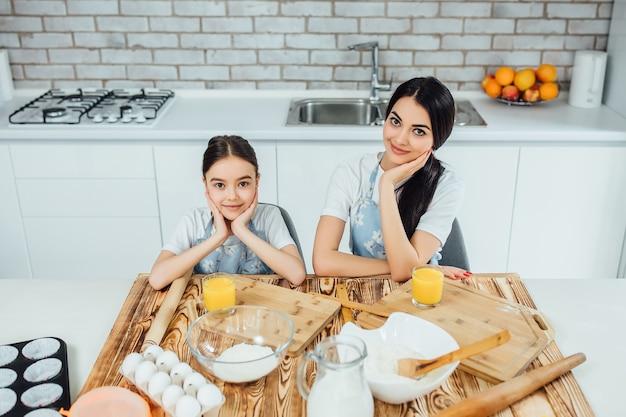 Lustige schwestern bereiten den teig vor, backen kekse in der küche