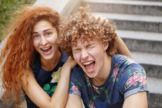 Lustige sommersprossige frau mit rötlichem buschigem haar, das den kopf ihrer freundin kratzt, die augen schließt und mund öffnet. verliebtes paar, das laut lacht