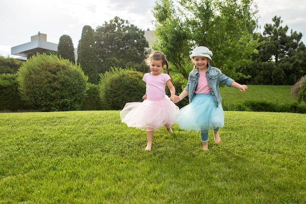 Lustige starts. kindermode-konzept. gruppe von jugendlich mädchen, die am park laufen. kinder bunte kleidung, lebensstil, trendige farbkonzepte.