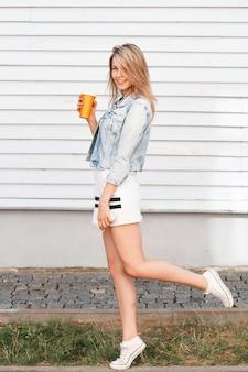 Lustige stilvolle junge frau im trendigen sportkleid in blauer jeansjacke in weißen turnschuhen mit einer orangefarbenen tasse mit einem cocktail, der spaß im freien nahe der holzwand hat. charmantes mädchen, das sich ausruht.