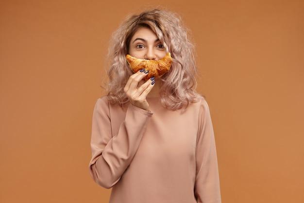 Lustige stilvolle junge frau in langärmeligem oberteil, das gegen leeren orangefarbenen wandraum herumalbert und frisch gebackenes croissant über ihrem gesicht hält