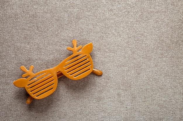Lustige stilvolle kinder spielen die billige gelbe plastiksonnenbrille, die auf hellem kindheits-, spiel- und modekonzept lokalisiert wird.