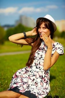 Lustige stilvolle sexy lächelnde schöne junge frau modell im sommer hellen hipster stoff kleid im hut sitzen auf gras im park